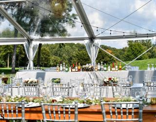 clear top structure tent with chiavari chairs and farm tables