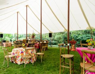 tables and chairs under sailcloth tent